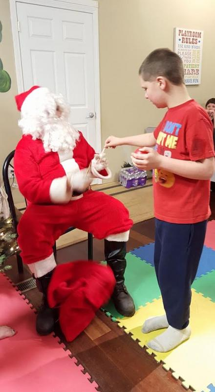 6cf912a8cb Santa gets down on the floor to play with kids in an autism play ...
