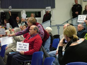 Opponents of the proposed propane terminal hold up signs in protest of the Searsport Planning Board's decision to end public comment with a dozen citizens waiting in line to speak. (Photo by Ethan Andrews)