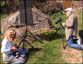 Cynthia MacDonald and Dennis Steinauer photograph dandelions for the Kansas to Oz class. (Photo by Chris Wolf)