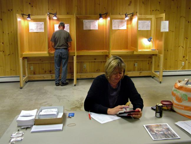 Searsmont Selectman Christopher Staples, background, fills out his ballot on Sept. 17, while Election Moderator and Warden Tammy Roberts passes a quiet moment at the polls. Searsmont was one of two towns to hold votes on withdrawing from Regional School Unit 20 on the same day as an eight-town vote on the district's budget. (Photo by Ethan Andrews)
